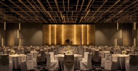 A Century City ballroom with ample space, rows of tables with chairs and a large stage.