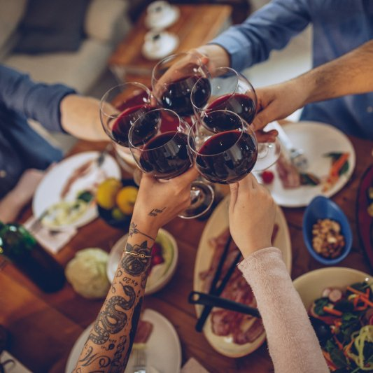 A group cheers glasses of red wine together.