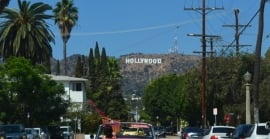 A red car drives down a street in LA, and the Hollywood sign is seen in the background.