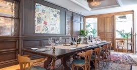 View of The Writer's Den, a private dining room complete with a large wooden table set with tableware and wine bottles.