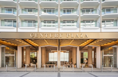 A straight on look at the gold and white façade of the Century Plaza