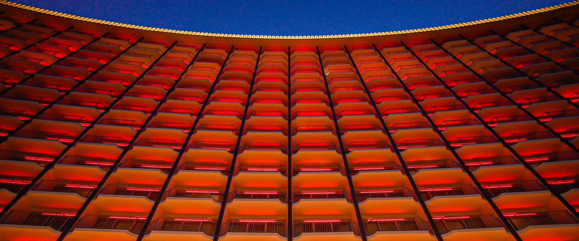A view of the Fairmont Century Plaza many balconies, illuminated in red and organge.
