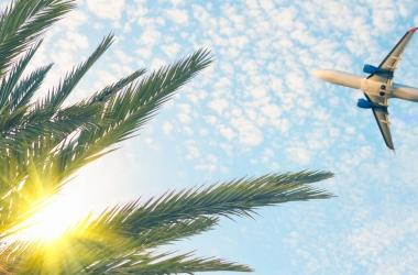 A plane flies overhead across blue skies.