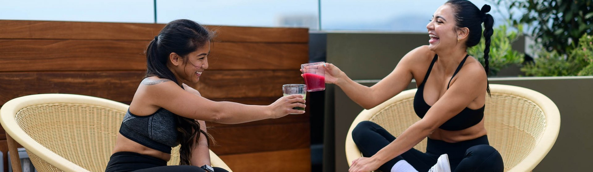 Women at the fitness center cheers drinks white relaxing.