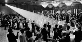 A spotlight shines on a crowd off men and women dressed up for Lyndon B. Johnson's entrance at Fairmont Century Plaza.