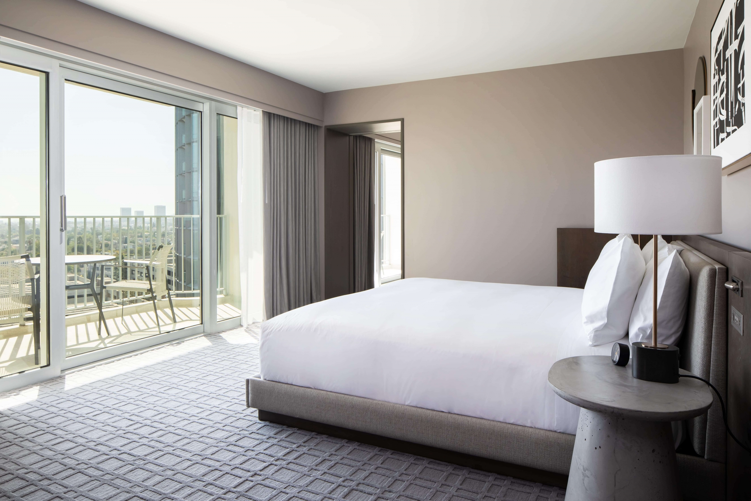 A clean hotel bedroom with balcony access through french doors.